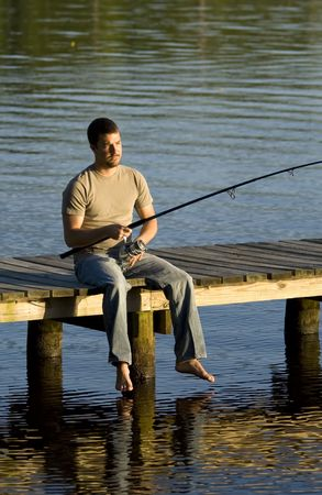 Man sitting on a dock fishing into a bay as the sun is setting. photo