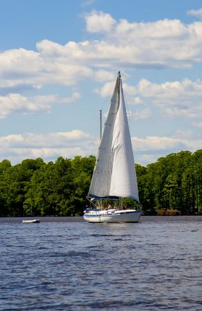 Sailboat yacht cruising down a river on a sunny and cloudy day. Stok Fotoğraf
