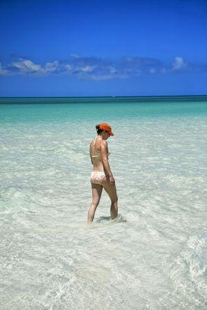 sandbar: Female walking along an endless perfectly clear white sandbar, looking down in the water splashing as she walks. Stock Photo