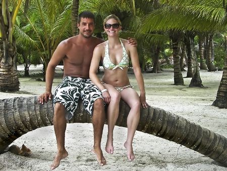 Young man and women smiling and sitting on a bent over palm tree in the middle of a tropical island covered with palm trees.