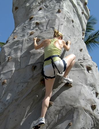 strenuous: Young lady climbing a rock wall in the tropics.