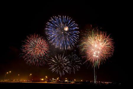Firework dislpay viewed at night exploding over a bridge. Stock Photo - 3177090