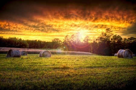 Beautiful sunset lighting a field with hay rounds producing brilliant and amazing colors. Stock Photo - 3256991