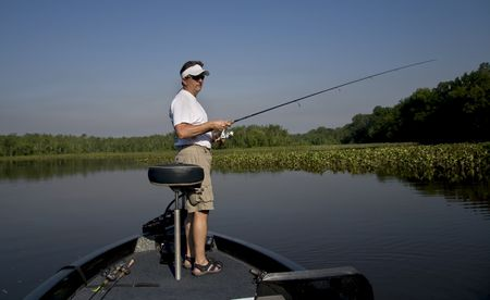 resting rod fishing: Man fishing in a river off the front of his bass boat.
