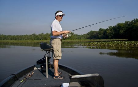 Man fishing in a river off the end of his bass boat. Stock Photo