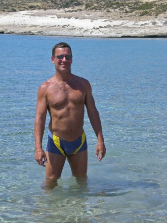 Man wearing a bathing suit standing in tropical cove with clear blue water. Фото со стока