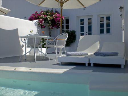 산토리니 (Santorini) 섬의 수영장이 딸린 아름다운 발코니가있는 고급스러운 객실입니다. 스톡 콘텐츠