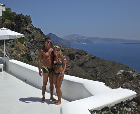 Happy couple enjoying vacation and the scenic view of Santorini Island from there luxurious rooms balcony. Stock Photo