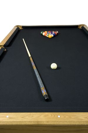 Black felt top pool table with billiards, cue ball, and stick on top.