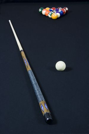 Black felt top pool table with billiards, cue ball, and stick laying on top.