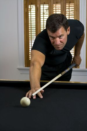 lining up: Man lining up the cue ball to break the billiards on the other end of the pool table. Stock Photo