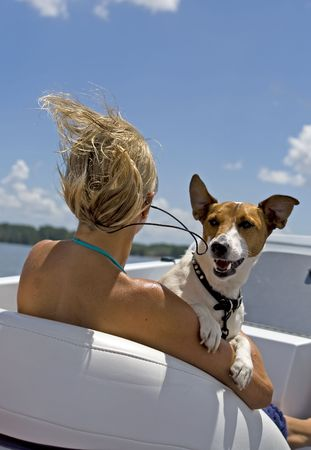 Woman and jack russel enjoying a fast boat ride.