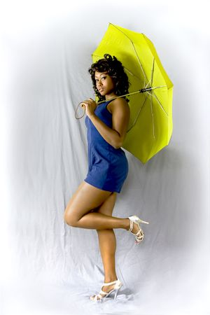 Young attractive African American female possing pin-up style with a green umbrella. Stock Photo - 3588622