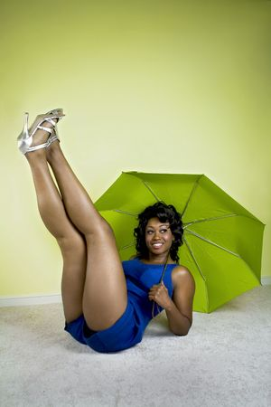 Young attractive African American posing pin-up style holding a green umbrella. Stock Photo - 3588619
