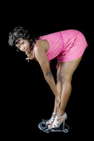 bend over: Attractive African American standing on scale looking surprised about her weight.