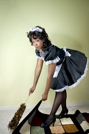 Maid caught sweeping under the rug.