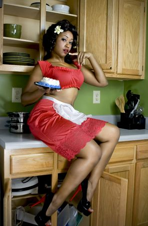 Attractive African American eating cake off her finger, sitting on kitchen counter.