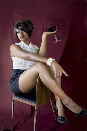 Sexy female posing with martini glass while sitting on a chair. Фото со стока