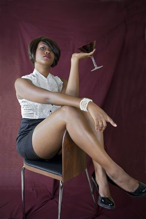 Sexy female posing with a martini glass, while sitting on chair. photo