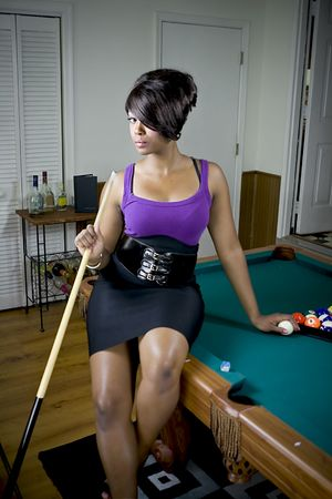Sexy female sitting on pool table, hold pool stick.