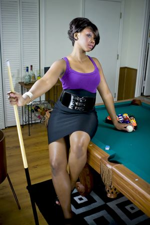 Sexy female sitting on pool table, holding pool stick. Stock Photo - 3588620