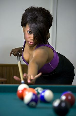 Attractive female playing a game of pool.