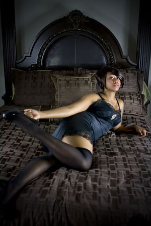 Sexy female laying on bed wearing lingerie. photo