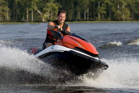 Man riding wave runner in river enjoying a nice summer day. Stock Photo