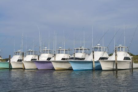 Row of multi-colored nice deep sea fishing boats in a marina. photo