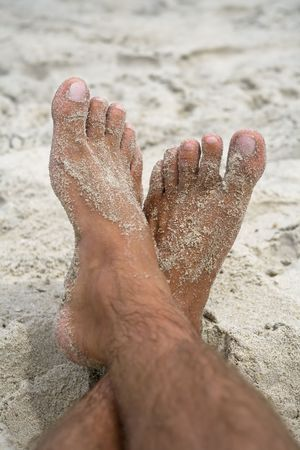 Mans feet crossed as he relaxes on the beach.