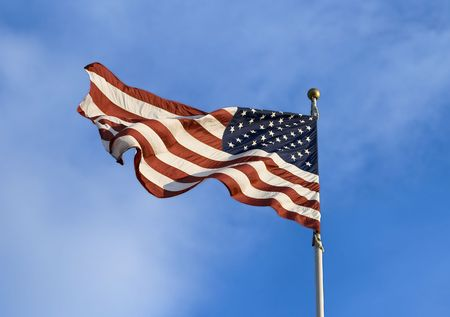 American flag blowing in the wind with blue sky in background.