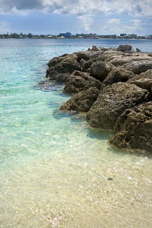 Tropical beach with rocks extending into the ocean. photo