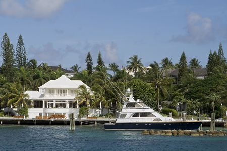 Large and luxury white home in the tropics with a large deep sea fishing boat in dock. Stock Photo