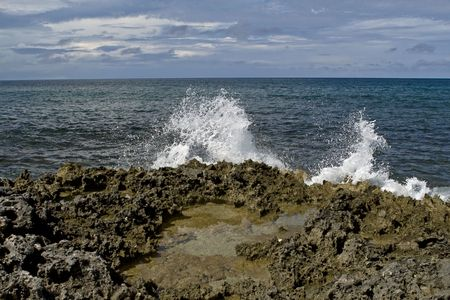 volcanic stones: Volcanic shoreline with wave splashing as it collides into the rocks.