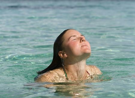 wet suit: Young woman surfacing from clear green water after a refreshing swim in the tropics. Stock Photo