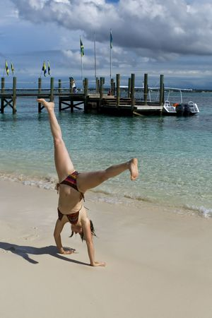 inverted: Young woman doing a cartwheel on a tropical beach. Stock Photo