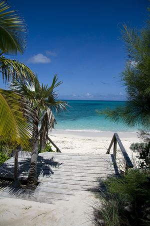Entrance to a beautiful tropical beach with clear green water.
