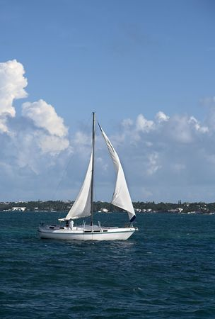 Small sailboat sailing through tropical water. photo