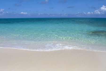 Beautiful tropical shoreline with clear green water and wave rolling up on white sandy shore.