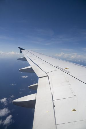 View of commercial airplane wing during a flight over water.