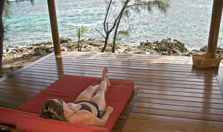 Young woman laying in beach hut on a tropical island. photo