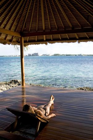 Young woman relaxing and laying in a beach hut on a tropical island. photo
