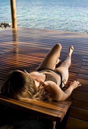 젊은 여성 열 대 섬에 해변 오두막에 누워.