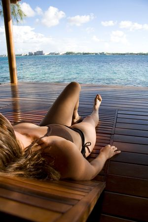 Young woman laying in a beach hut on a tropical island. Stock Photo