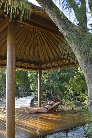 Young woman laying in a beach hut on a tropical island. photo