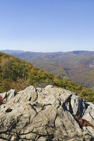 Rocky cliff over looking a mountain range during autumn leaf change over. Stock Photo - 4080624
