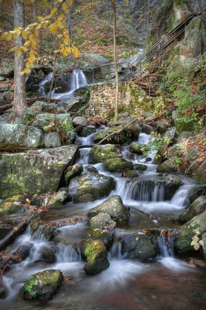 Autumn scene of waterfall in the mountains. photo