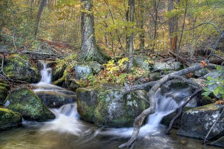 Autumn view of waterfall in the woods of mountains. photo