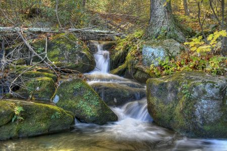 Beautiful autumn waterfall in the woods of mountains. photo