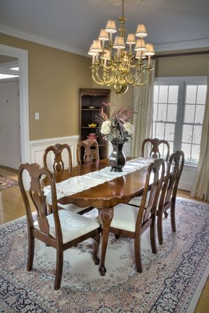 dining table and chairs: Luxurious wooden dining room table and chairs in a modern home. Stock Photo